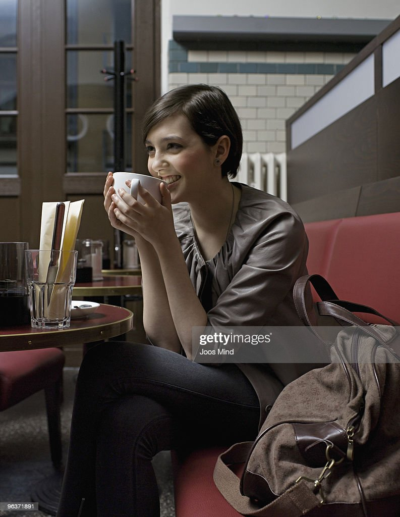 woman in cafe holding cup, laughing : Stock Photo