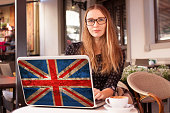 Woman sitting in a cafe with cup of coffee and notebook with flag of Great Britain on it. English language learning concept