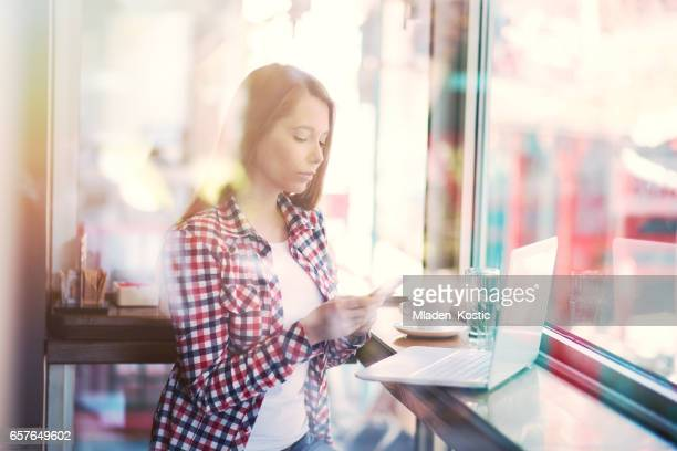 Woman in cafe sending text message