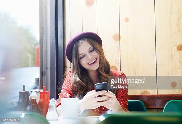 woman in cafe smiling and texting on phone