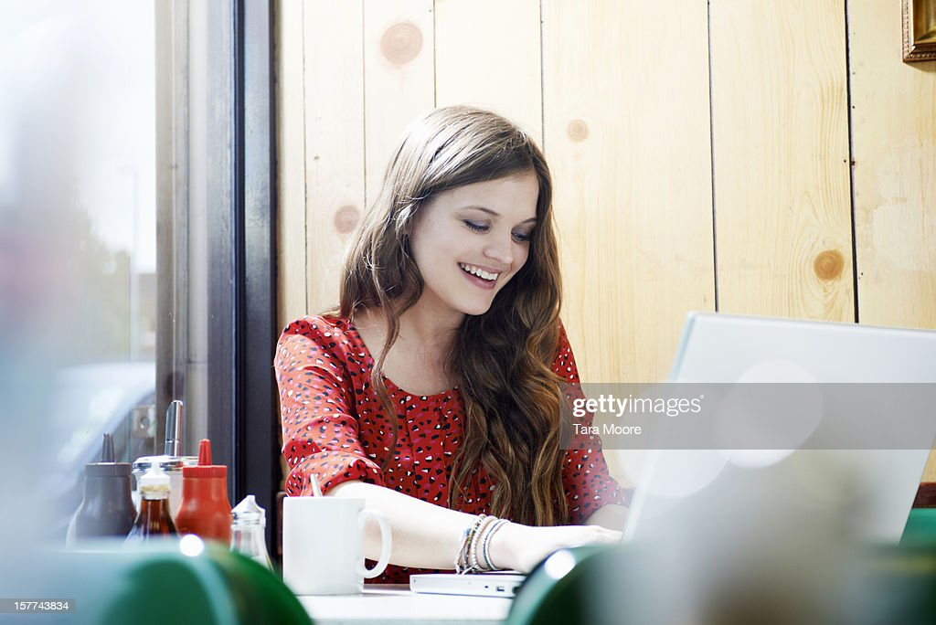 woman in cafe smiling using laptop : Stock Photo