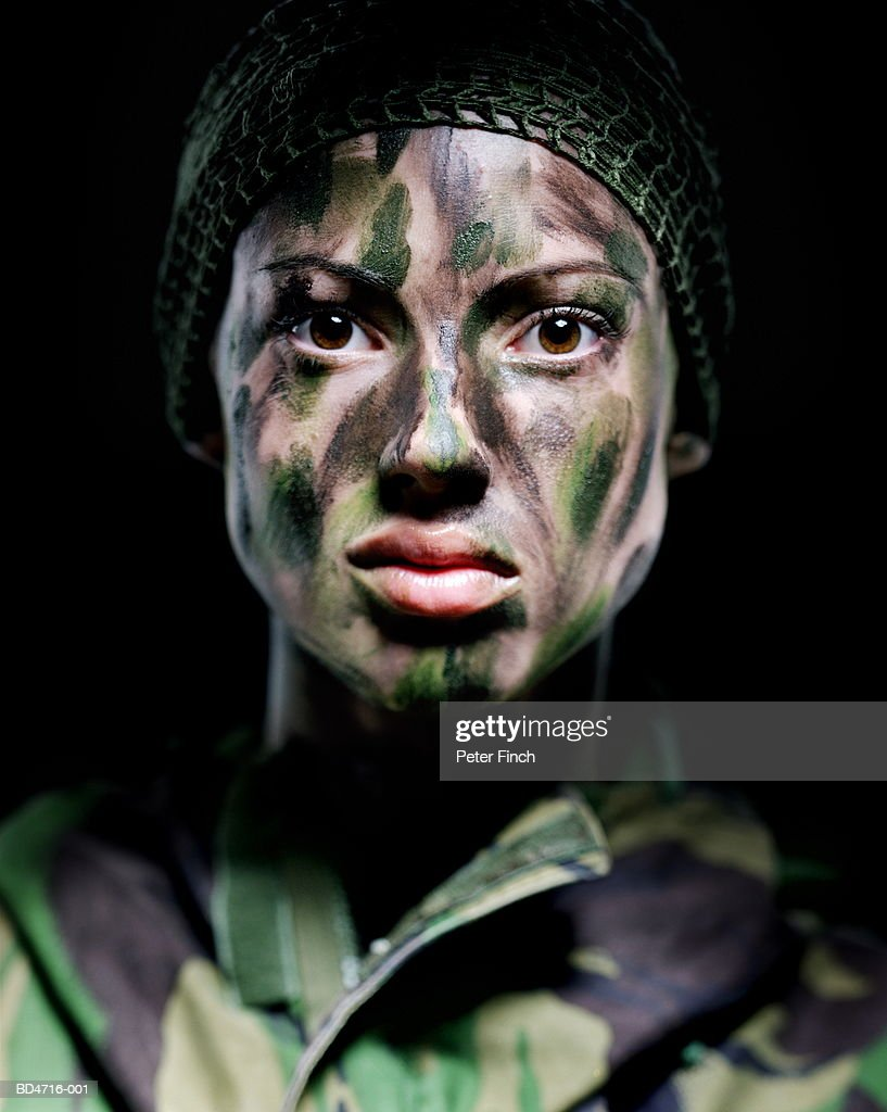 Woman in camouflage clothing and face paint, portrait