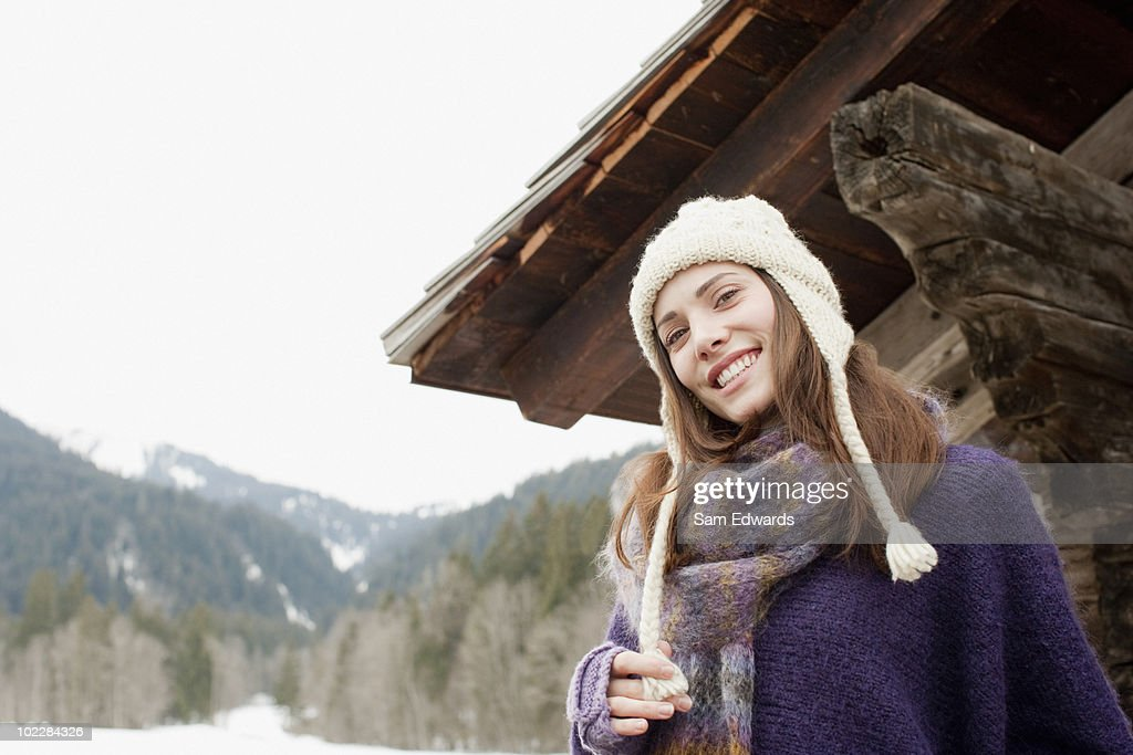 Woman in cap and scarf standing outdoors