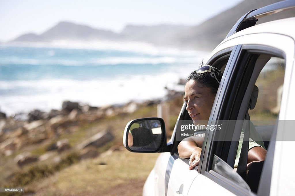 Woman in car by the sea : Stock Photo