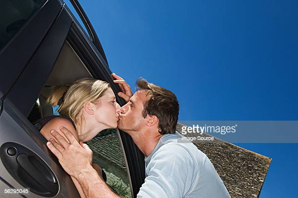Woman in car kissing boyfriend
