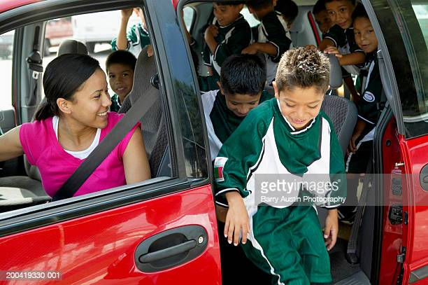 Woman in car looking at boys (7-11) football team getting out