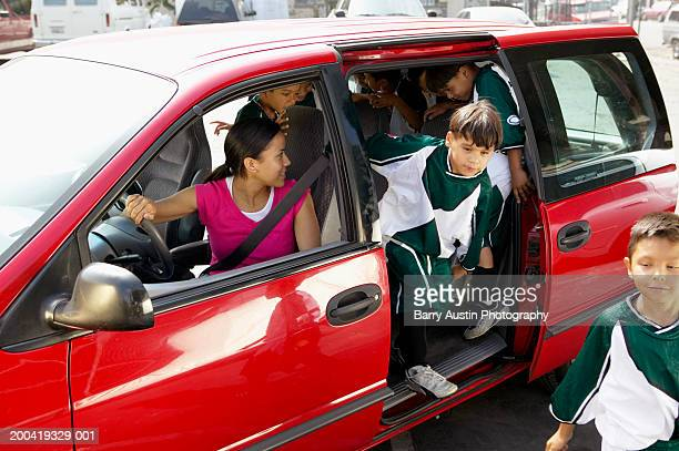 Woman in car looking at boys (7-11) football team in back
