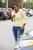 African American woman (30s) standing in parking lot, shopping for car.  Shallow DOF, focus on woman.