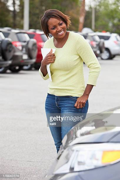Woman in car lot holding brochure