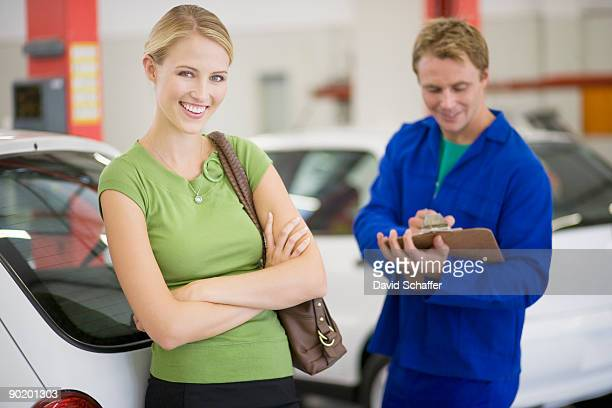 Woman in car showroom with service man
