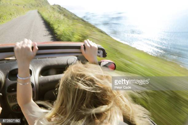 Woman in car with roof down driving along coast road