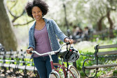 A woman in casual clothes in the park pushing a bicycle.