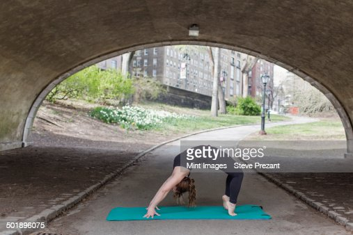 A woman in Central Park, in a black leotard and leggings, doing yoga. : Stock Photo