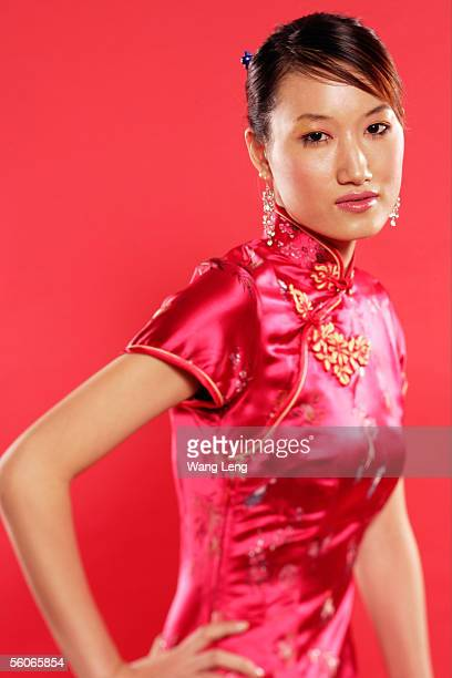 Woman in Cheongsam, hand on hip, looking at camera