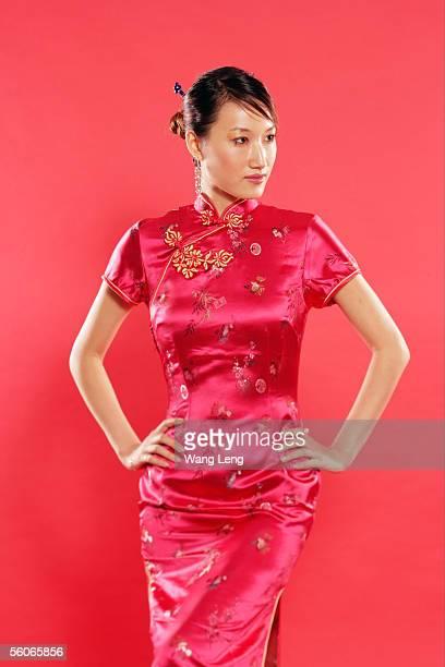Woman in Cheongsam, hand on hips, looking away