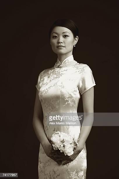 Woman in cheongsam holding bouquet of flowers, portrait