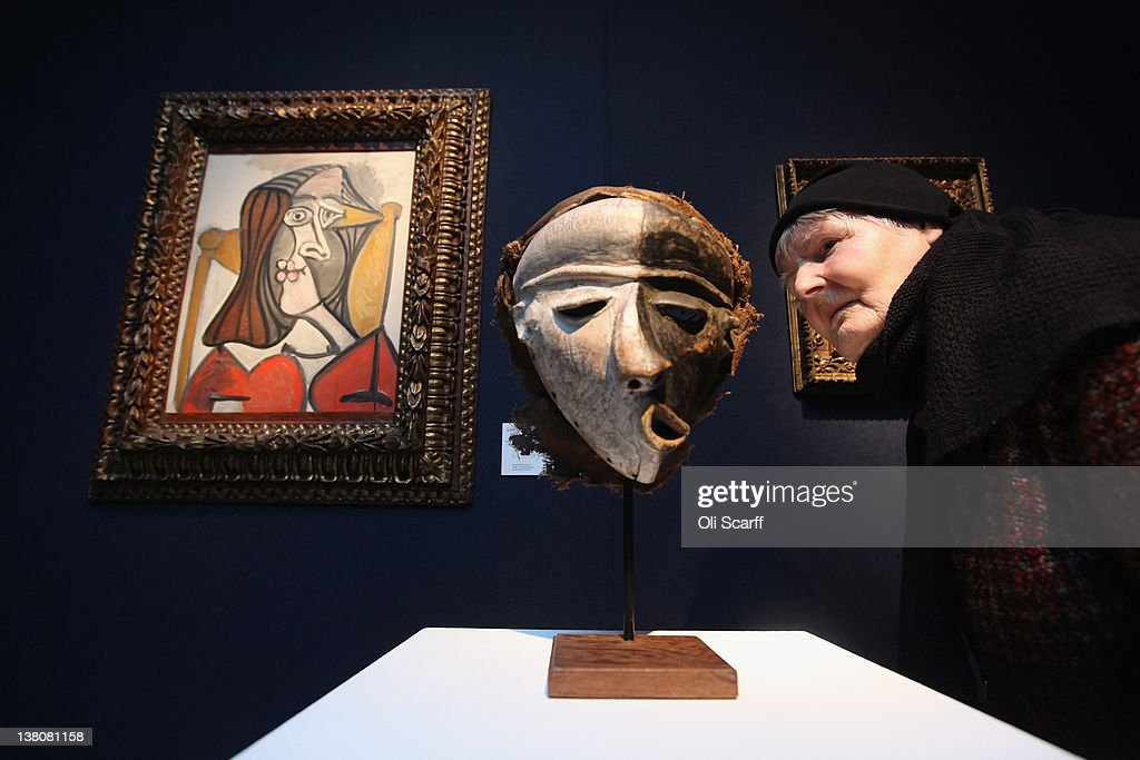 A woman in Christie's auction house admires a painting by Pablo Picasso entitled 'Femme au fauteuil' and a Pende Mask from the Democratic Republic of Congo on February 2, 2012 in London, England. The painting, which is estimated to fetch 6 million GBP, and the mask are being auctioned in Christie's forthcoming sale 'Living with Art' which will take place on February 9, 2012 and February 10, 2012.
