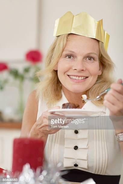 Woman in Christmas crown eating dessert