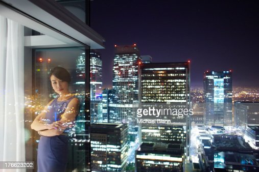Woman in City apartment at night : Stock Photo