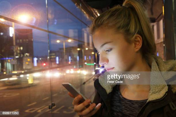 Woman in city at night looking at phone