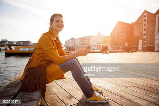 Woman in city enjoyng sun.