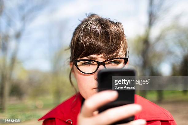 Woman in city park looking at smartphone