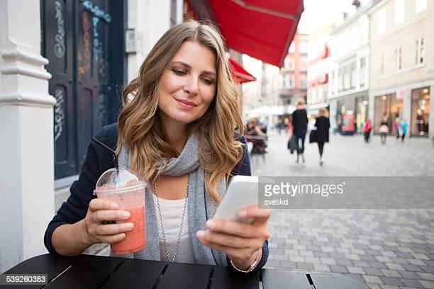 街の女性のスマートフォンを使用しています。