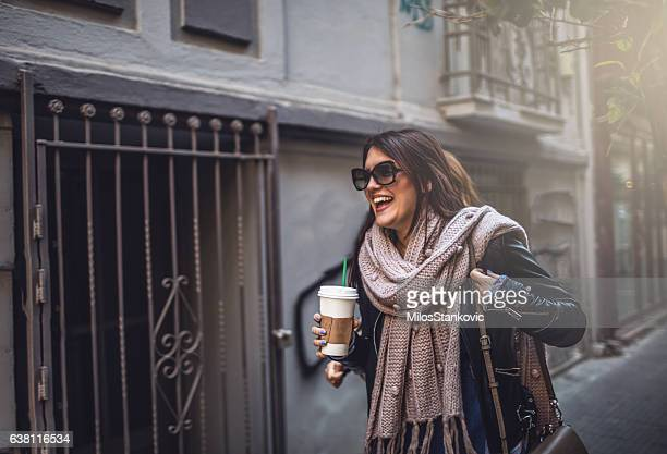 Woman in city walk with coffee