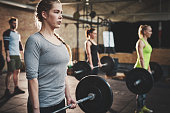 Serious muscular young woman with ponytail and gray shirt performing dead lift barbell exercises with three other trainees