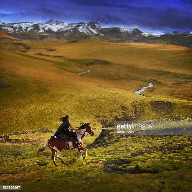 Woman in cloak rides horse through lush valley