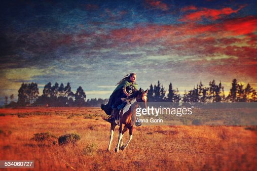 Woman in cloak rides paint horse at sunrise