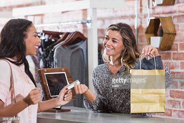 Woman in clothing store paying at checkout counter