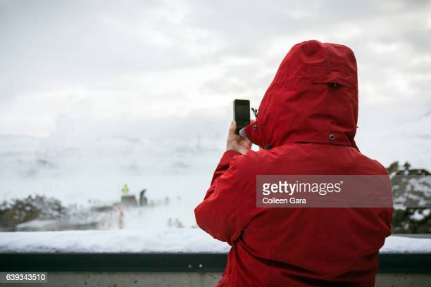 Woman in Coat Takes a Photo of the Blue Lagoon in Iceland