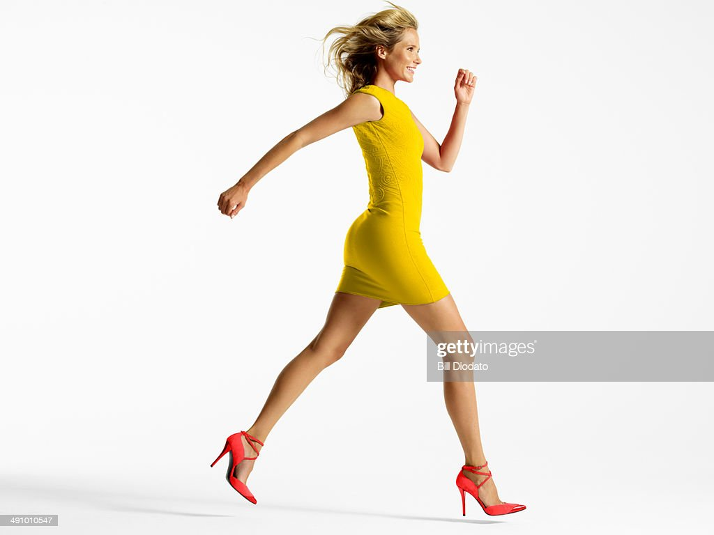 Woman in colorful dress jumping in studio : Stock Photo