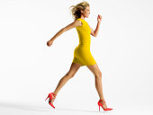 Woman in colorful dress jumping in studio