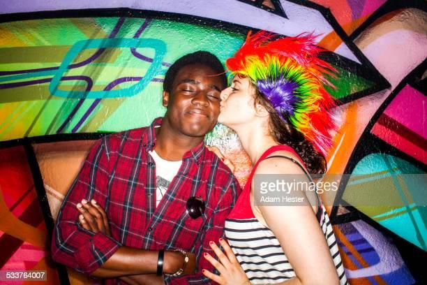 Woman in colorful wig kissing boyfriend near graffiti wall