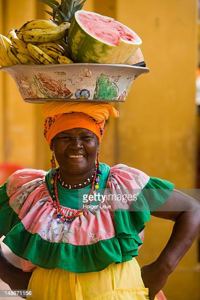 Woman in colourful traditional attire carrying bowl of tropical fruit on her head.
