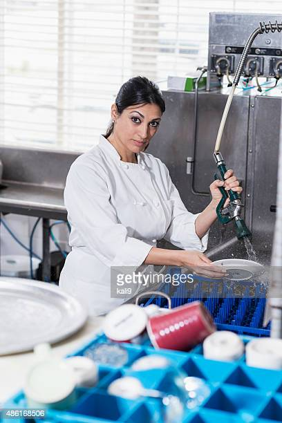 Woman in commercial kitchen at sink cleaning dishes