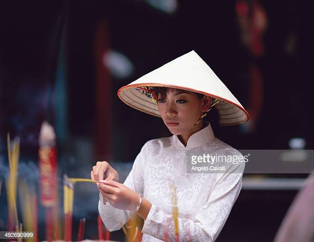 Woman in Conical Hat Lighting Incense