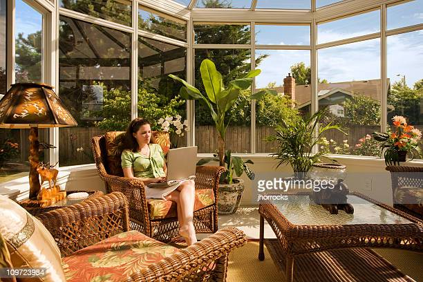 Woman in Conservatory Working on Laptop