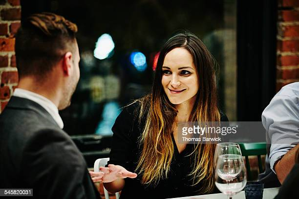 Woman in conversation with friend during dinner