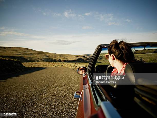 Woman in convertible looking at reflection