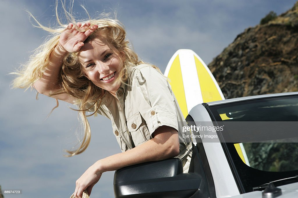 Woman in convertible with surfboard : Stock Photo