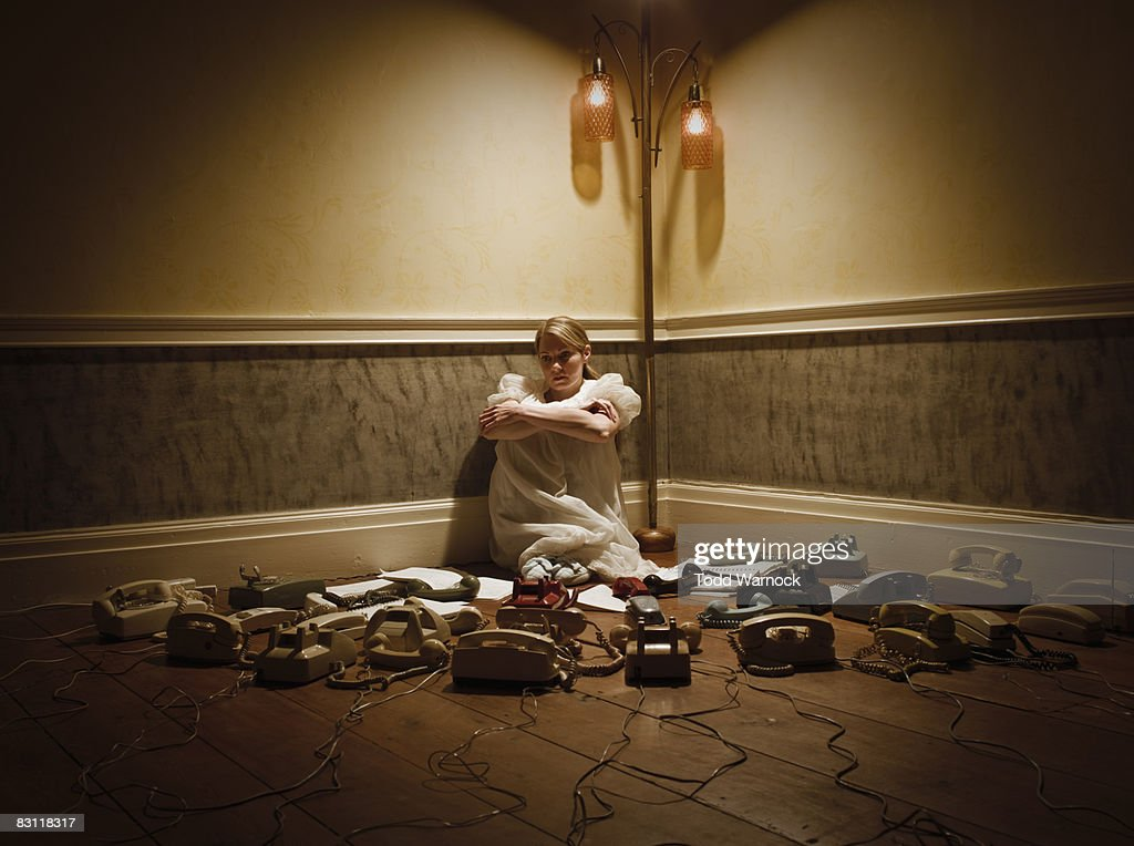woman in corner surrounded by phones : Stock Photo