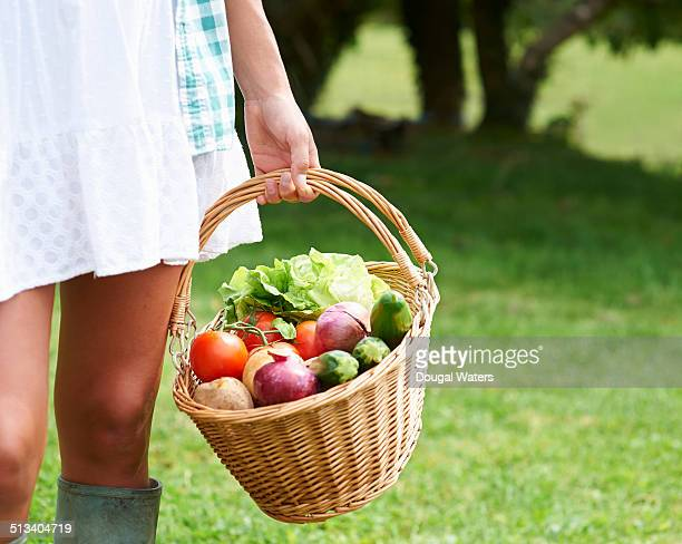 Woman in countryside holding basket of vegetables.