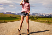 Woman in cowboy boots in front of mountains