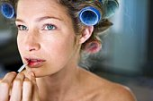 Woman in curlers putting on lipstick