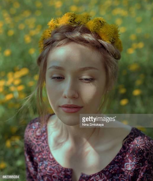 Woman in dandelion wreath in dandelion field