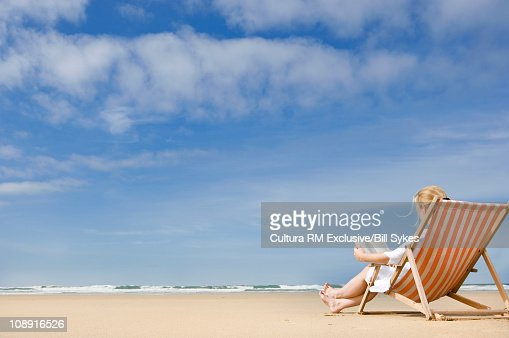 Woman in deck chair on beach : Stock-Foto