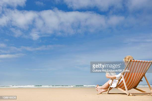 Woman in deck chair on beach